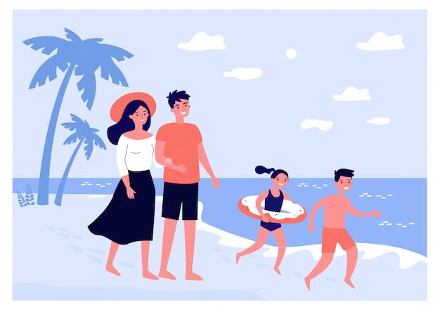 Coppia di genitori felici e bambini che trascorrono l'estate in riva al mare