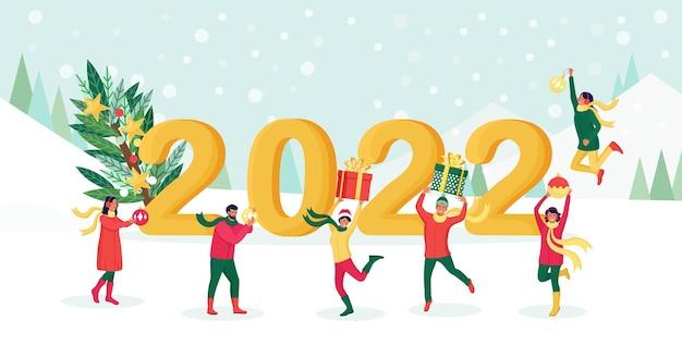Gente felice che salta con scatole regalo, palline decorative, palline con numeri 2022 sullo sfondo. gli amici augurano buon natale e felice anno nuovo. saluto di festa. gente allegra che festeggia il natale