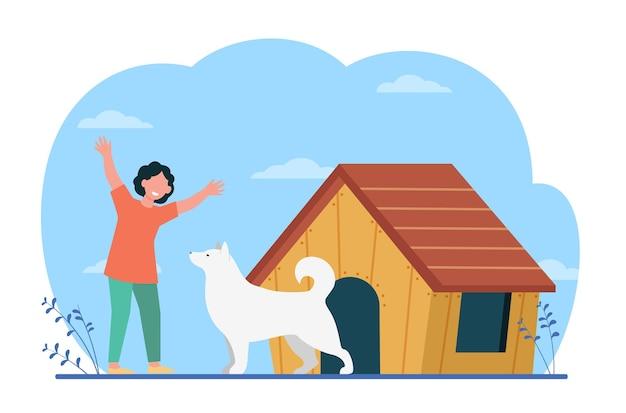 Ragazzo felice del ragazzo del proprietario dell'animale domestico con il cane vicino alla cuccia