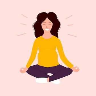 Donna incinta felice che si siede nella posa di yoga