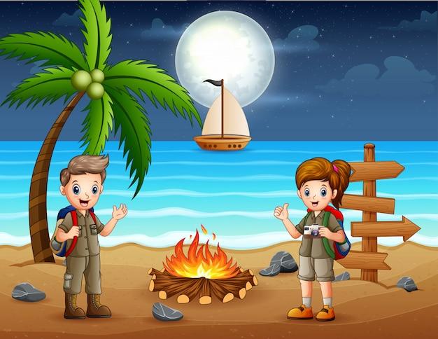 Bambini scout felici che godono del falò in spiaggia