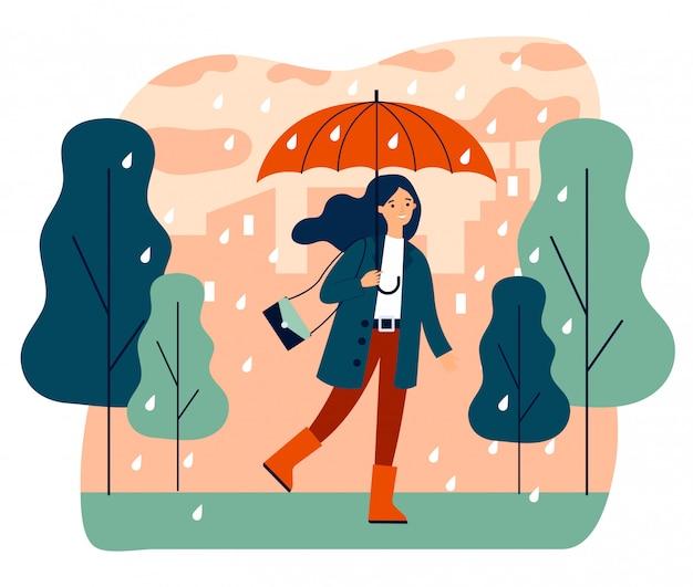 Ragazza sorridente felice con l'ombrello che cammina nel giorno piovoso