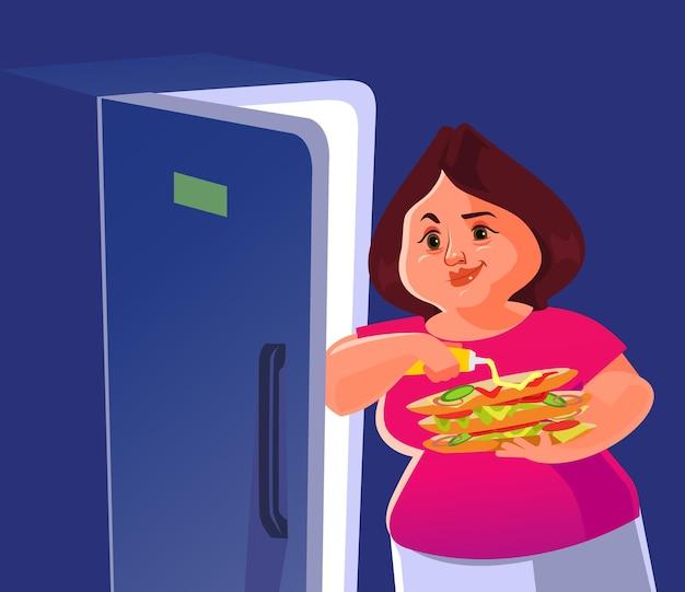 Donna sorridente felice in piedi vicino al frigorifero e mangia hamburger