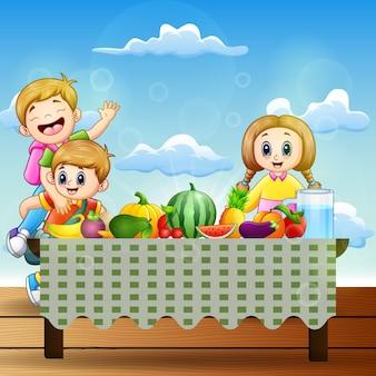 Due bambini felici con piatti di molti tipi di frutta