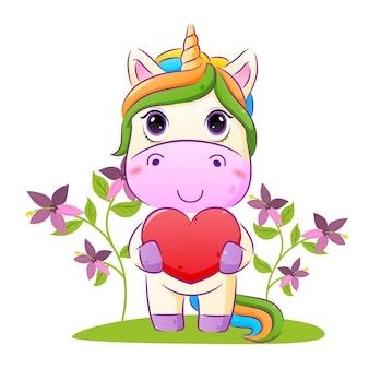 L'unicorno felice tiene in mano un grande amore e sta in piedi nell'illustrazione del giardino dei fiori