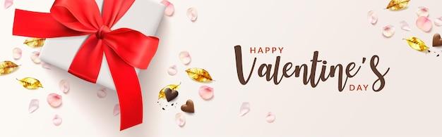 Felice banner romantico di san valentino. scatola regalo bianca e fiocco rosso, foglie dorate, forma di cuore di cioccolato, petali di rosa rosa.