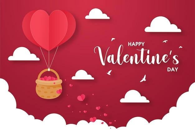 Felice giorno di san valentino biglietto di auguri. un palloncino a forma di cuore che galleggia nel cielo con un cesto pieno di cuori rossi