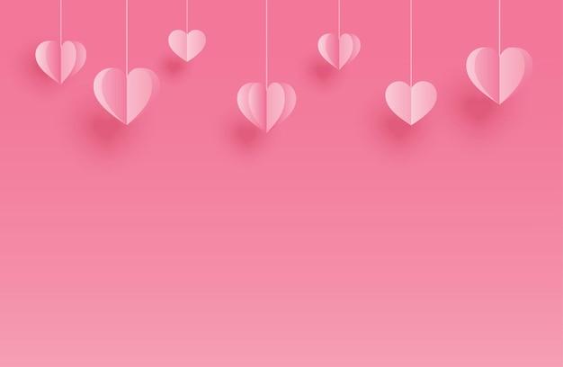 Auguri di felice giorno di san valentino con cuori di carta appesi su sfondo rosa pastello.