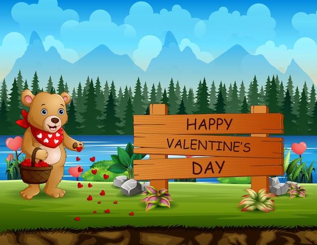 Segno felice di giorno di biglietti di s. valentino con l'orso che tiene un cestino
