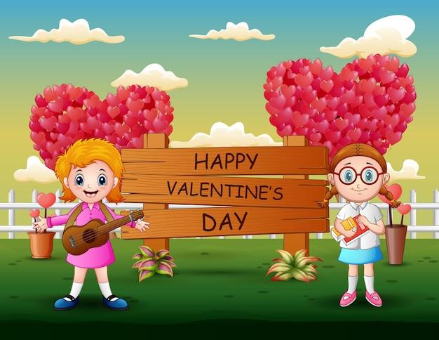 Segno felice di giorno di biglietti di s. valentino con le ragazze che stanno