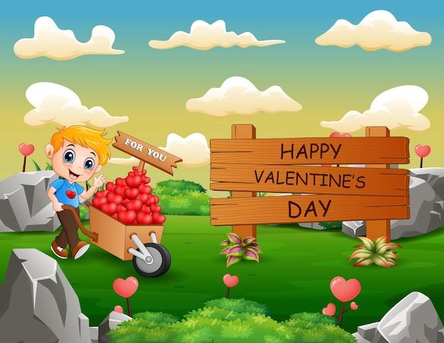 Segno di legno felice di giorno di biglietti di s. valentino con il ragazzo che spinge un carrello