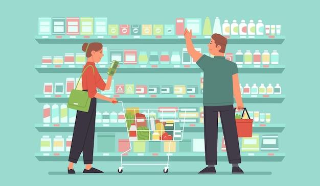 Gli acquirenti felici di una donna e di un uomo in un mercato di alimentari scelgono il cibo sugli scaffali