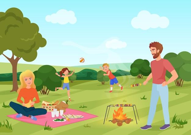 Famiglia felice youg su un picnic nel campo della foresta. padre, madre, figlio e figlia stanno giocando e riposano nella natura.