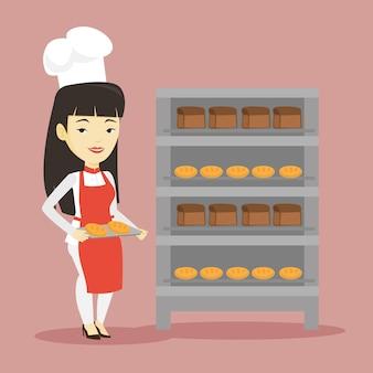 Giovane panettiere femminile felice che tiene vassoio di pane.