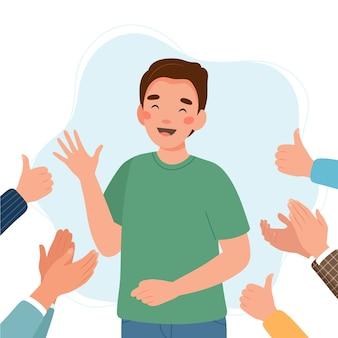 Felice giovane uomo circondato da mani con i pollici in su e applaudire