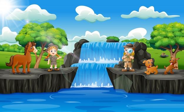 Ragazzo e ragazza felici dello zookeeper nella scena della cascata Vettore Premium