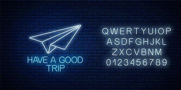 Buon viaggio banner al neon incandescente con segno di aeroplano di carta e alfabeto sul muro di mattoni scuri