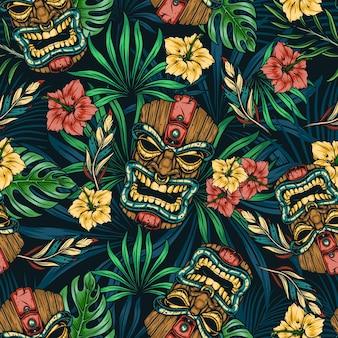 Modello senza cuciture colorato tropicale hawaiano con maschera tiki tribale, ibisco, monstera e foglie di palma