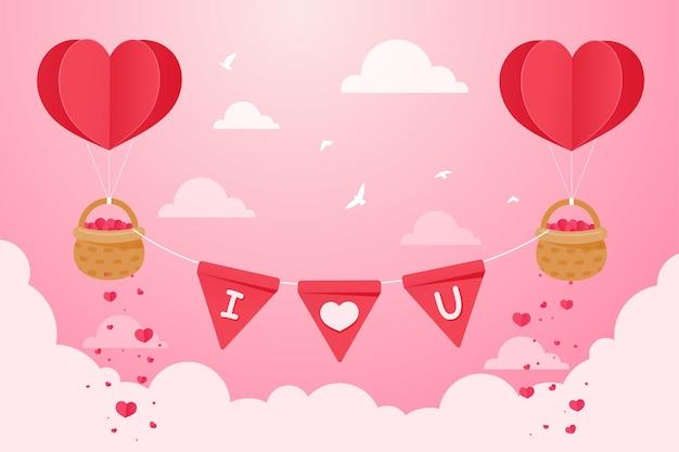 Un palloncino a forma di cuore che galleggia nel cielo con un cesto pieno di cuori rossi
