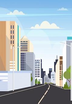 Verticale piano del fondo di grattacieli delle costruzioni moderne dell'orizzonte della città della strada asfaltata della strada principale