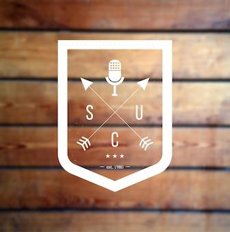 Scudo con logo hipster con frecce incrociate e microfono retrò a podcast in legno sfocato o spettacolo in piedi