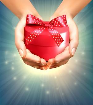 Sfondo vacanza con le mani che tengono il contenitore di regalo. concetto di dare regali.