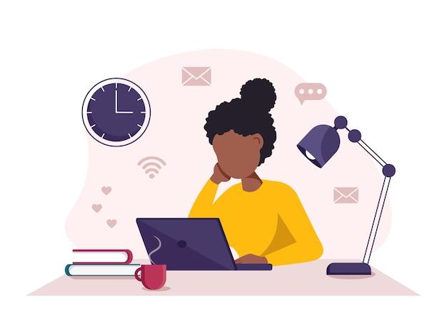 Donna di colore di concetto del ministero degli interni con il computer portatile che lavora dallo studente domestico o dal libero professionista