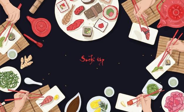 Modello di banner orizzontale con tavolo ristorante asiatico pieno di cibo giapponese e mani che tengono sushi, sashimi e panini con bacchette su sfondo nero.