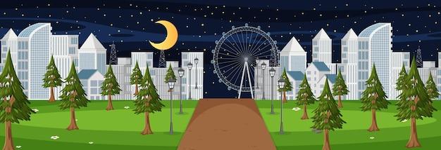 Scena orizzontale con una lunga strada che attraversa il parco fino alla città di notte