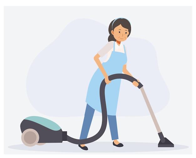 Governante che pulisce il pavimento con l'aspirapolvere.