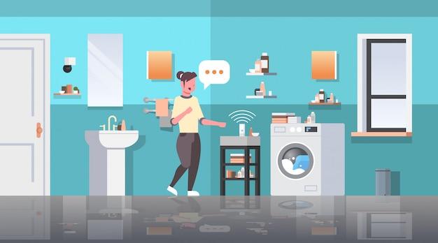 Casalinga che utilizza il riconoscimento vocale degli altoparlanti intelligenti attivati assistenti digitali automatizzati rapporto di comando concetto moderno bagno interno piano orizzontale a figura intera