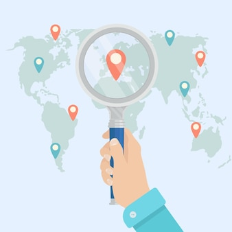 Mano umana che tiene la lente d'ingrandimento per trovare la migliore destinazione di viaggio per il viaggio sulla mappa del mondo