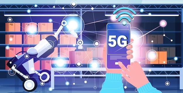 Mano umana utilizzando un'app mobile che controlla il caricatore robotico 5g connessione al sistema wireless online quinta generazione di internet concetto innovativo