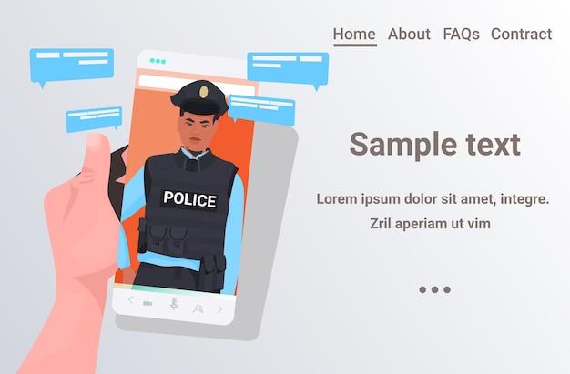 Mano umana utilizzando smartphone in chat con il poliziotto durante la comunicazione online di videochiamata