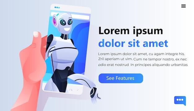 Mano umana utilizzando smartphone con persona robotica femmina sullo schermo comunicazione online intelligenza artificiale concetto di tecnologia ritratto spazio copia copy