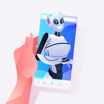 Mano umana utilizzando smartphone con persona robotica femminile sullo schermo comunicazione online concetto di tecnologia di intelligenza artificiale ritratto