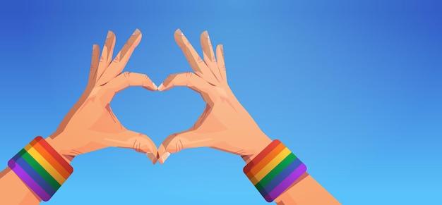 Gesto delle mani umane a forma di cuore bandiera arcobaleno lgbt gay lesbica amore parata pride festival concetto di amore transgender