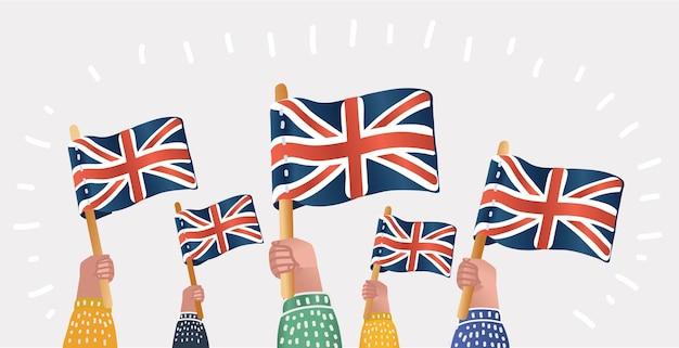 Le mani umane tengono le bandiere inglesi della gran bretagna