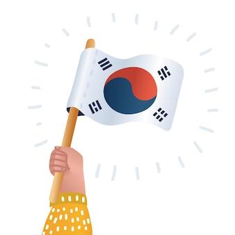Le mani umane tengono la bandiera della corea del sud
