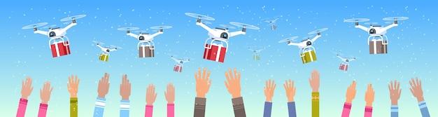Mani umane sollevate droni offrendo regalo presente scatole cielo trasporto spedizione posta aerea concetto di consegna espressa