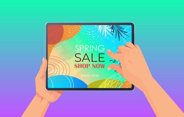 Mani umane utilizzando tablet pc con volantino banner vendita di primavera o biglietto di auguri sullo schermo illustrazione orizzontale
