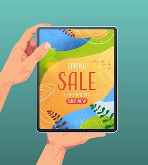 Mani umane utilizzando tablet pc con volantino banner vendita di primavera o biglietto di auguri sullo schermo illustrazione verticale