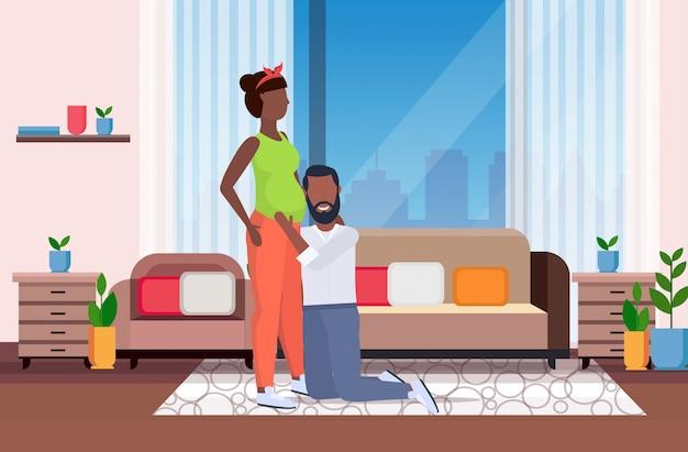 Marito in ginocchio ascoltando la famiglia della pancia della moglie incinta in attesa di gravidanza neonato concetto di genitorialità moderno salotto interno orizzontale a figura intera