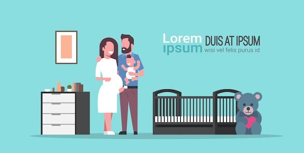 Marito con moglie incinta che tiene il figlio neonato in piedi vicino al presepe