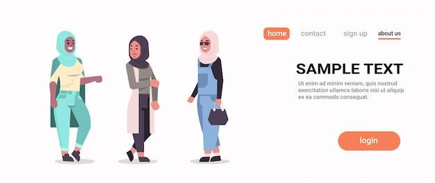Donne ic in hijab discutendo di ragazze arabe che indossano il velo tradizionale vestiti in piedi insieme concetto di comunicazione piena lunghezza orizzontale copia spazio piatto