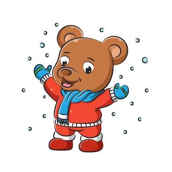 L'illustrazione dell'orso bruno con il maglione e la sciarpa rossi sta giocando nella neve