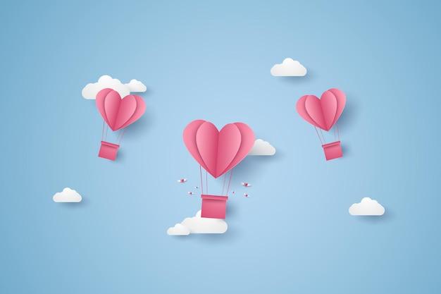 Illustrazione dell'amore con una mongolfiera a cuore rosa che vola nel cielo in stile arte cartacea