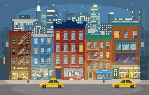 Illustrazione della notte di manhattan con case retrò con negozi e taxi e grattacieli in background. città di notte. paesaggio urbano. skyline notturno. stile piatto.