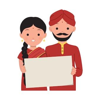 Uomo indiano e donna che tengono un cartello in bianco