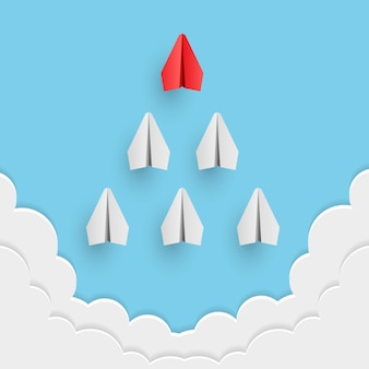 L'aereo di carta rosso individuale guida l'altro. concetto di business e leadership